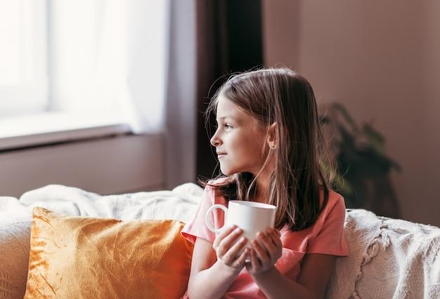 Маленькая девочка сидит с белой чашкой на диване в гостиной
