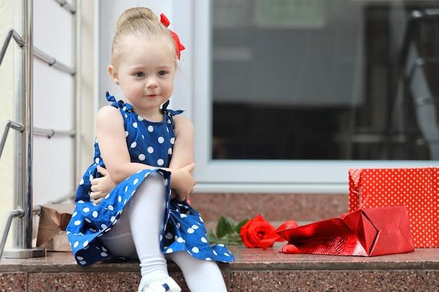 Маленькая девочка сидит с разноцветными сумками на ступеньках торгового центра.