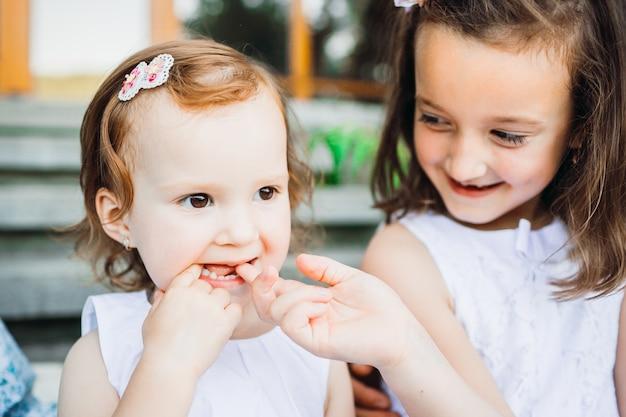 Маленькая девочка сидит со своей сестрой по стопам