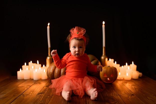 Маленькая девочка сидит с тыквами и свечами