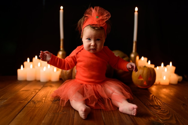 Little girl sits with jack pumpkins and candles