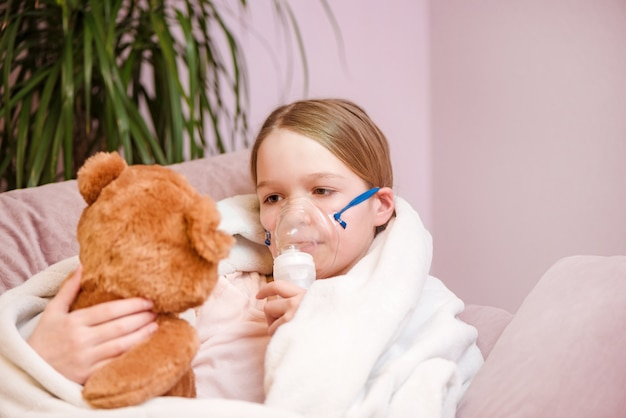 Little girl sits with toy on sofa at home in a mask for inhalations, making inhalation with nebulizer at home inhaler.