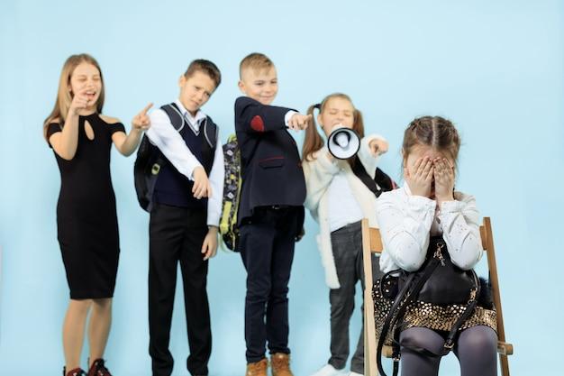 一人で椅子に座って、子供たちが嘲笑しながらいじめの行為に苦しんでいる少女