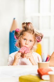 Маленькая девочка сидит и ест мороженое