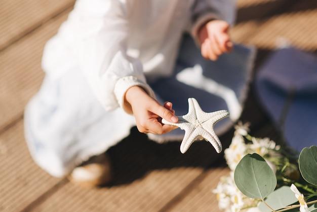 Маленькая девочка сидит и держит морскую звезду летом и детей