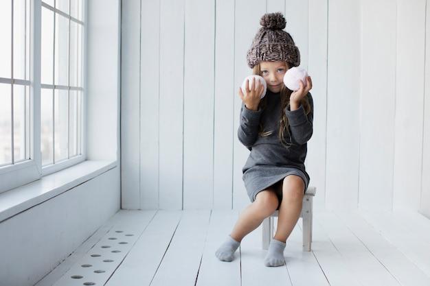 Маленькая девочка сидит и держит снежки