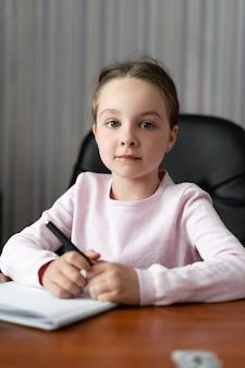 Маленькая девочка сидит дома за столом.