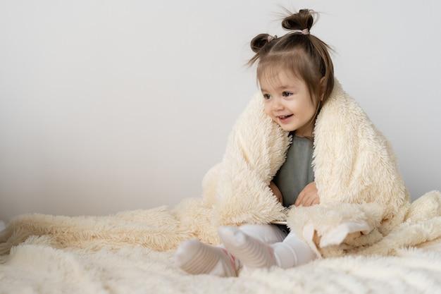 Маленькая девочка сидит дома на кровати. она укрылась одеялом и весело улыбается. место на белой стене для текста.