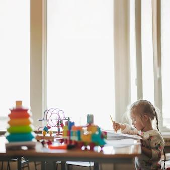 장난감으로 테이블에 앉아 어린 소녀
