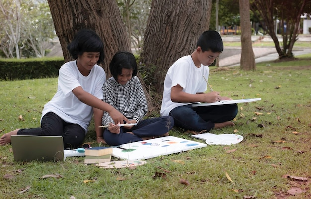Маленькая девочка сидит посреди младшей сестры и ее брата. рисует цвет на холсте. они улыбаются со счастливым чувством, занимаясь вместе в парке