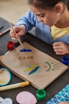 Маленькая девочка сидит за столом и рисует картину во время занятий по искусству