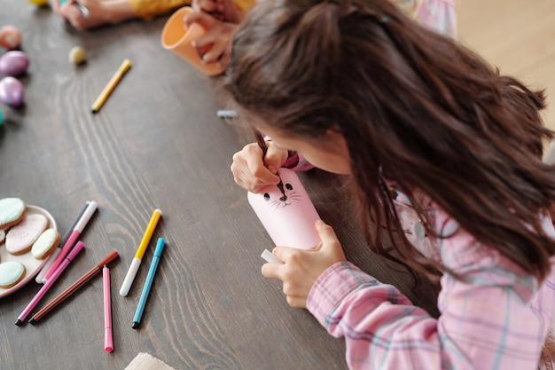 Маленькая девочка сидит за столом, лепит кролика из бумаги и рисует его карандашами