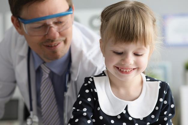 병원에서 남자 의사의 방문에 앉아 어린 소녀
