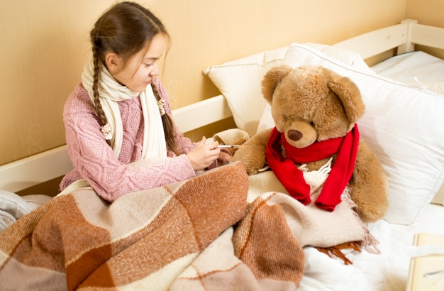 Little girl sitting on bed and doing injection to brown teddy bear