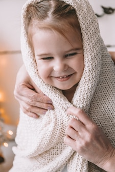 Little girl sitting on the bed wrapped in a blanket