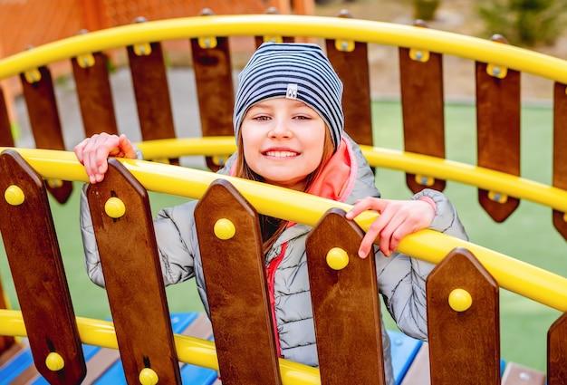 Маленькая девочка сидит за деревянным забором с желтыми металлическими перилами на детской площадке и улыбается