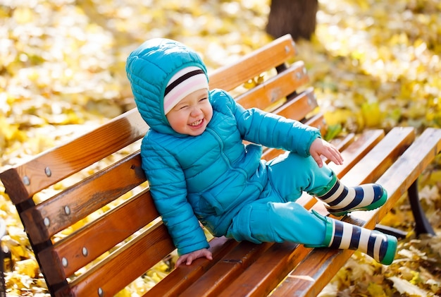 Little girl sitting on a bench in the park