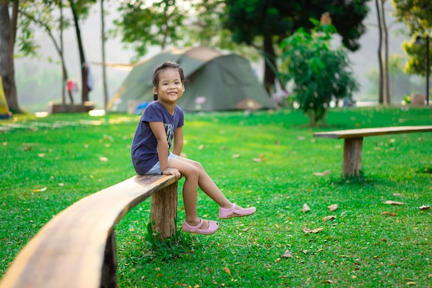 Little girl sitting on bench while going camping
