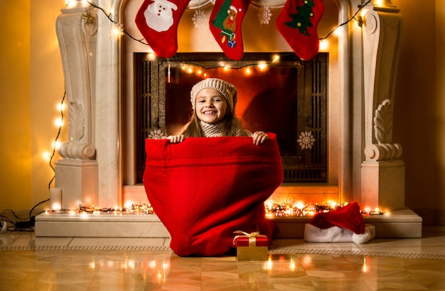 Little girl sitting in big red sack at room decorated for christmas