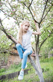 Little girl sitting on blossoming tree in apple garden