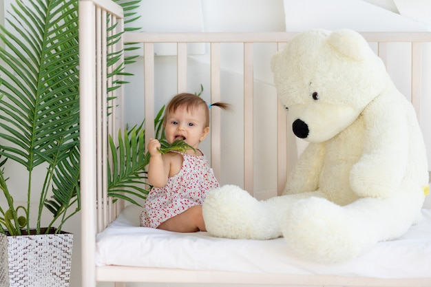Little girl sitting in a bright room in a crib at home with a big teddy bear
