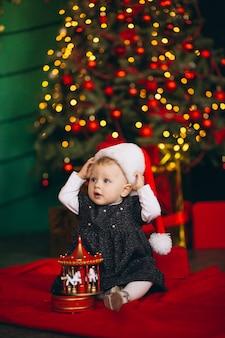 Маленькая девочка сидит у елки с игрушкой
