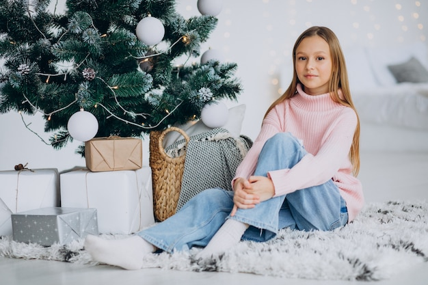 Bambina seduta da albero di natale