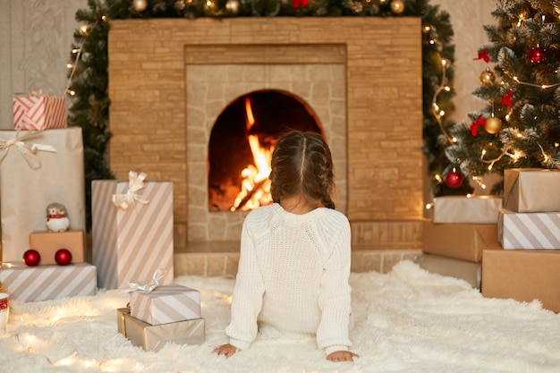 Little girl sitting by fireplace on christmas eve, looking at fire while sitting on soft carpet, waiting new year eve, wants to open her present boxes.