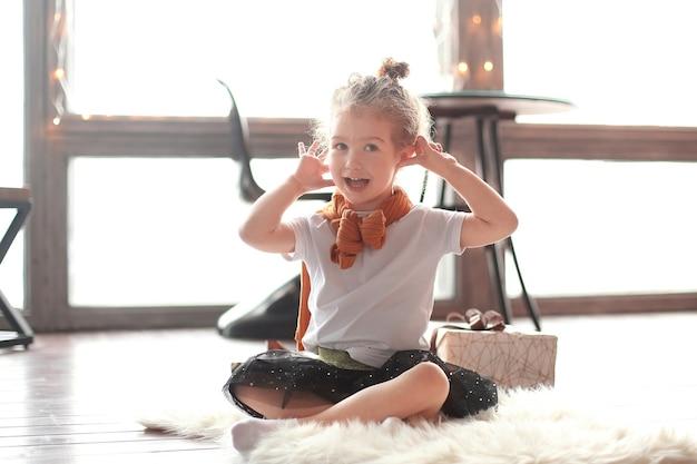 Little girl sitting on the carpet in the living room.