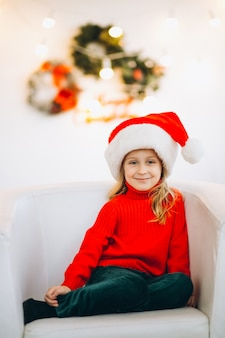 Little girl sitting in chair on christmas