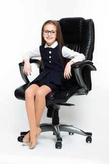 Little girl sitting in chair dressed as a businesswoman