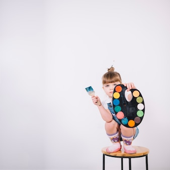 Little girl sitting on chair with palette and paint brush