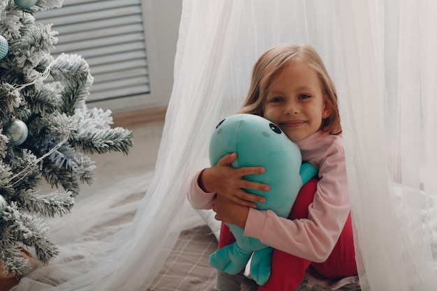 Little girl sitting in a children's room with a toy
