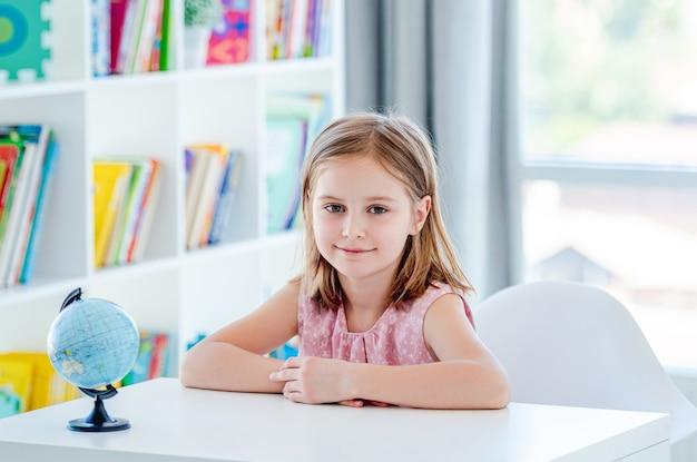 Little girl sitting at desk in light classroom