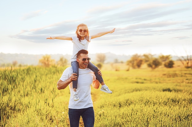 Little girl sitting on father's shoulders and laughing