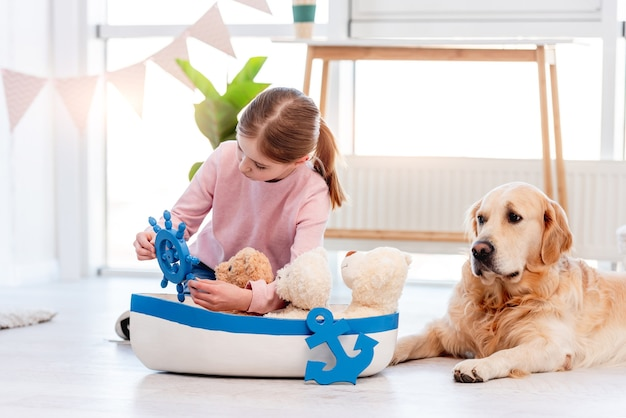 Little girl sitting on the floor and playing with sea ship with golden retriever dog