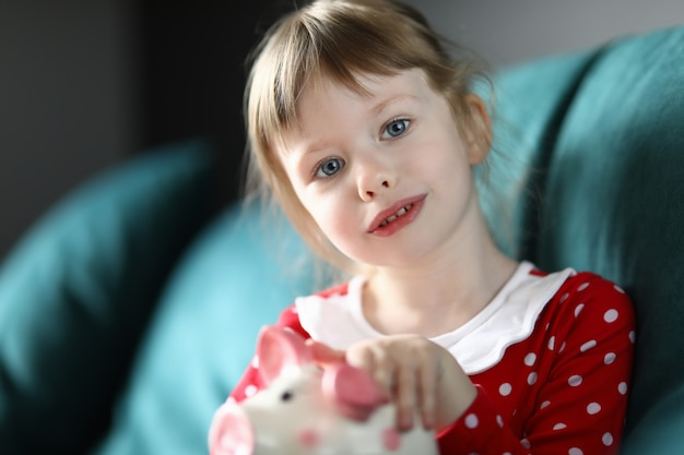 Little girl sitting at home sofa with piggy bank