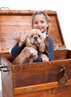 犬と一緒に箱に座っている少女は、白い背景にyesサインを示しています