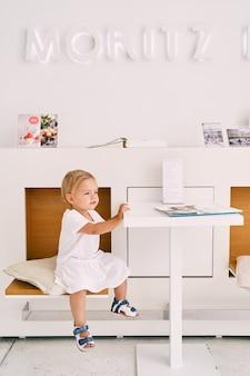 의자에 테이블에 카페에 앉아 어린 소녀