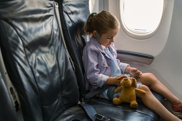 Маленькая девочка сидит в кресле с игрушкой и держит телефон во время поездки на самолете