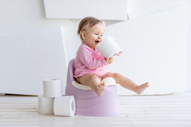 トイレットペーパーとピンクの服を着たトイレの白い部屋に座っている少女