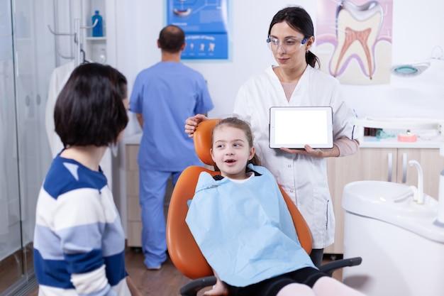 치과 의자에 앉아 있는 어린 소녀와 크로마 키가 있는 태블릿 pc를 사용하는 소아 치과 의사. stomatolog는 복사 공간이 있는 태블릿 pc를 들고 있는 엄마와 아이에게 치아 예방을 설명합니다.