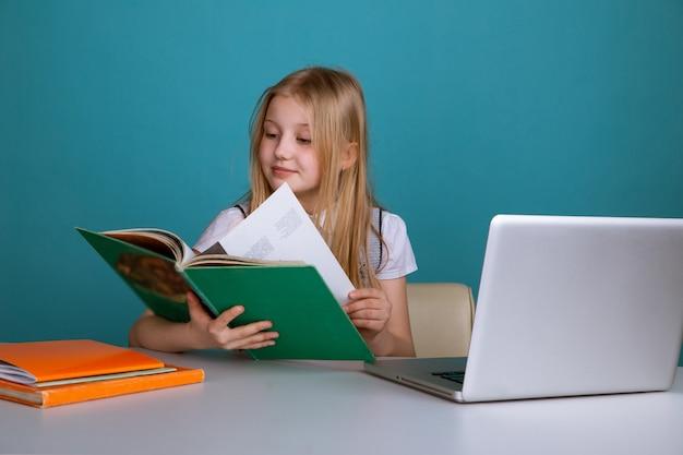 Маленькая девочка сидит в классе с книгой перед компьютером.