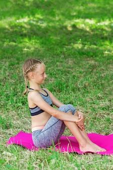Маленькая девочка сидит в общественном парке.