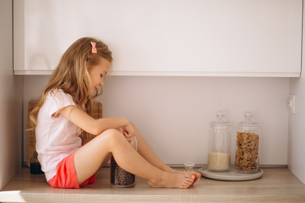 Little girl sitting at the kitchen