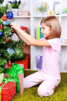 部屋のクリスマスツリーの近くに座っている少女
