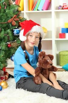 クリスマスツリーの近くに座っている少女