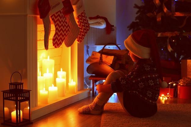 クリスマスのために飾られた暖炉のそばに座っている少女