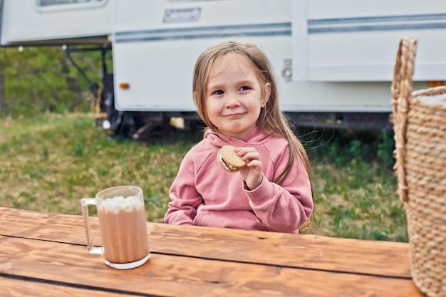 キャンピングカーの近くに座って、クッキーとローストマシュマロから作られたスモアを食べる少女