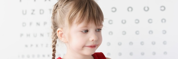 눈 검사를 위해 테이블 근처에 앉아 있는 어린 소녀